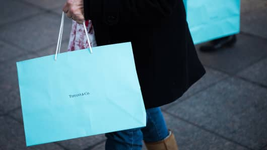 Shoppers carry Tiffany bags while walking on Fifth Avenue in New York.
