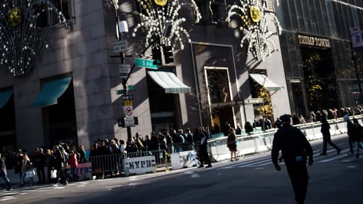 Pedestrians pass in front of the Tiffany & Co. flagship store on Fifth Avenue in New York, U.S., on Saturday, Nov. 26, 2016.