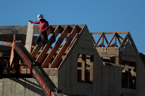 A worker stands on the roof of a home under construction at a new housing development on November 17, 2016 in San Rafael, California.