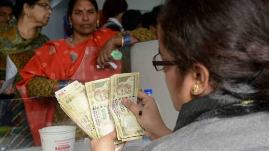 An Indian bank teller counts out notes as people gather inside a bank to deposit 500 and 1000 rupee notes at a bank in Amritsar on November 25, 2016.