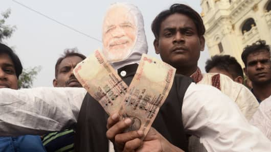 TMC activist with Narendra Modi's effigy and show Rs.1000 bank note during the rally. In leadership of Chief Minister Mamata Banerjee Trinamool Congress leaders, lakh of supporters take part in a protest march from College Street to Esplanade to protest against recent demonetization of bank note. Prime Mini