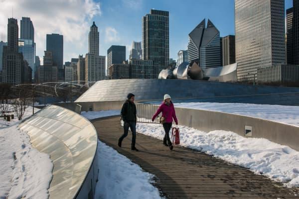 People walk on the pedestrian bridge through Millennium Park in Chicago.