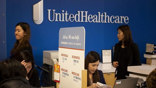 Representatives speak with customers at a UnitedHealthcare store in the Queens borough of New York, U.S., on Monday, Jan. 14, 2013.