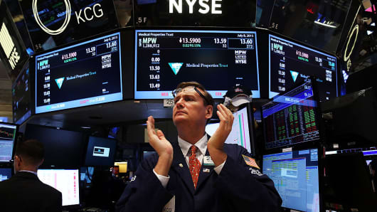A trader claps on the floor of the New York Stock Exchange (NYSE) at the close of the day on July 8, 2015 in New York City.