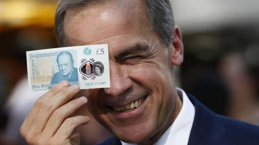 Bank of England governor Mark Carney poses with a new polymer five pound note on September 13, 2016 in London
