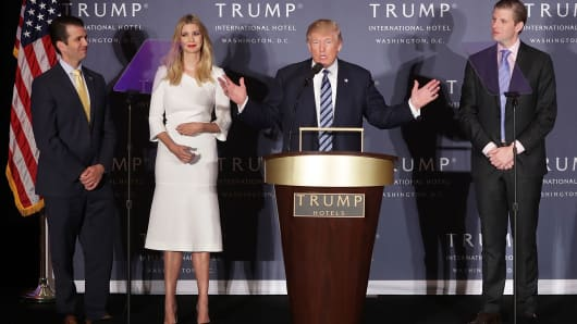 Republican presidential nominee Donald Trump (C) delivers remarks with his children (L-R) Donald Trump Jr., Ivanka Trump and Eric Trump during the grand opening ceremony of the new Trump International Hotel October 26, 2016 in Washington, DC.