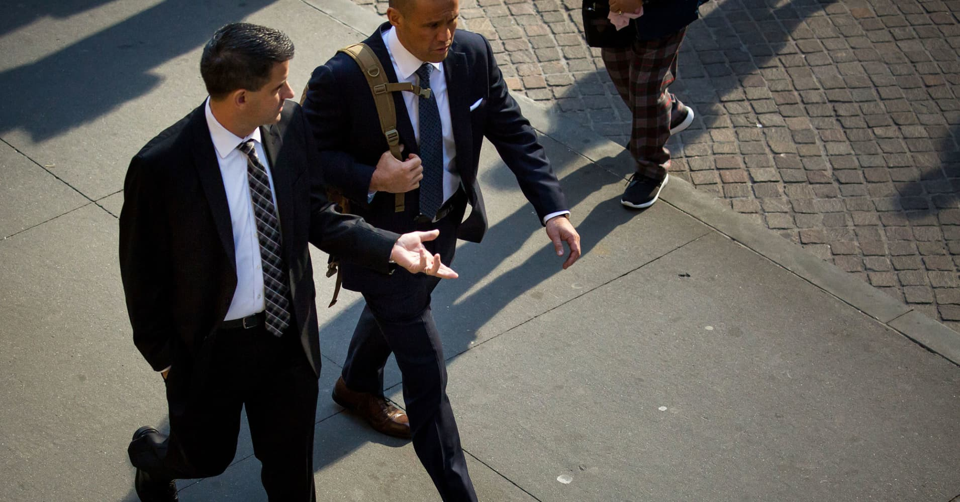 Men walk along Wall Street near the New York Stock Exchange in New York.