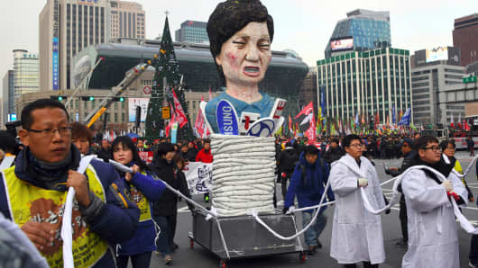 Protesters carry an effigy of South Korea's President Park Geun-Hye during an anti-government rally demanding the resignation of the president in central Seoul on November 30, 2016.