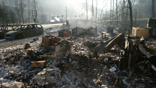 The remains of a business smolders after a wildfire November 29, 2016 in Gatlinburg, Tennessee.