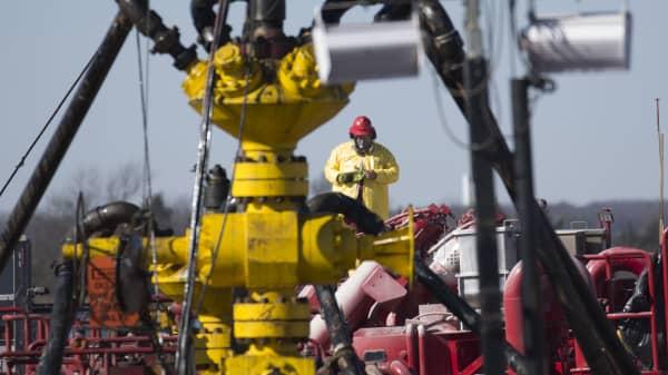 A Halliburton oil well fielder works on a well head at a fracking rig site January 27, 2016 near Stillwater, Oklahoma.