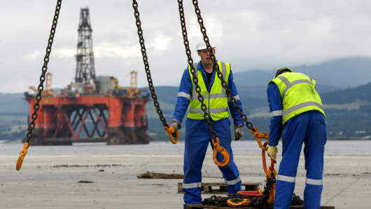 Employees attach hooks from a crane to a set of chains on the quay side, in view of the Ocean Vanguard mobile offshore drilling unit, operated by Diamond Offshore Drilling Inc. in the Port of Cromarty Firth in Cromarty, U.K., on Tuesday, July 26, 2016.