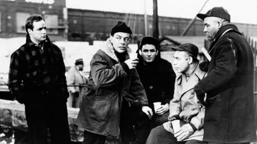 American actor and director Marlon Brando meeting some other dock workers on a bank in the film On the Waterfront.