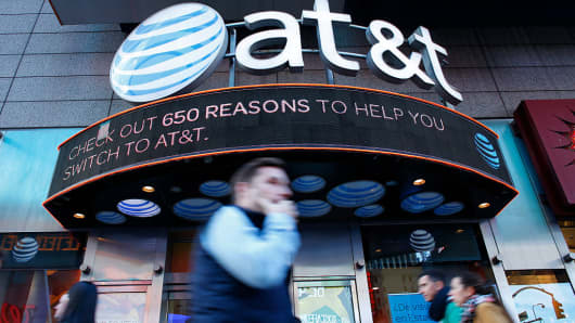 People walk past an AT&T store in New York on October 23, 2016.