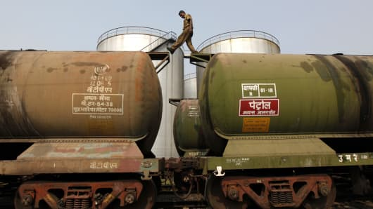 A worker walks atop a tanker wagon to check the freight level at an oil terminal on the outskirts of Kolkata.