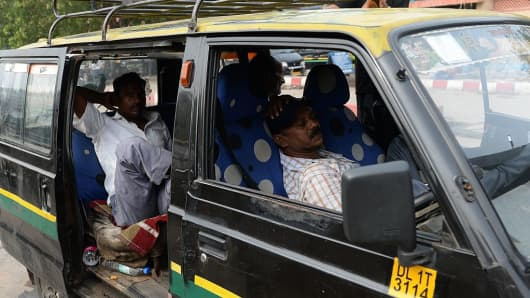 Indian taxi drivers rest in their taxis at the main railway station in New Delhi on July 26, 2016.