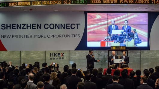 Hong Kong Exchanges and Clearing Ltd Chairman Chow Chung-kong (L) and Shenzhen Stock Exchange Executive Vice General Manager Jin Liyang pose with their conterparts in Shenzhen (on screen) before the start of the Shenzhen-Hong Kong Stock Connect on December 5, 2016. The long-delayed trading link between the Chinese city of Shenzhen and Hong Kong launched, opening another door to the mainland's cosseted stock markets.