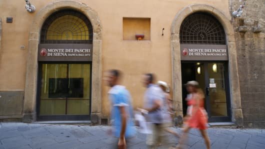 Pedestrians pass by a Banca Monte dei Paschi di Siena bank branch in Siena, Italy.