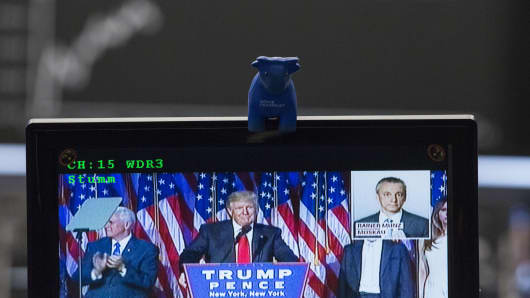 A toy bull figurine sits on a television screen as a news report shows U.S. President-elect Donald Trump delivering his victory speech following the U.S. presidential election result announcement, inside the Frankfurt Stock Exchange in Frankfurt, Germany, on Wednesday, Nov. 09, 2016.