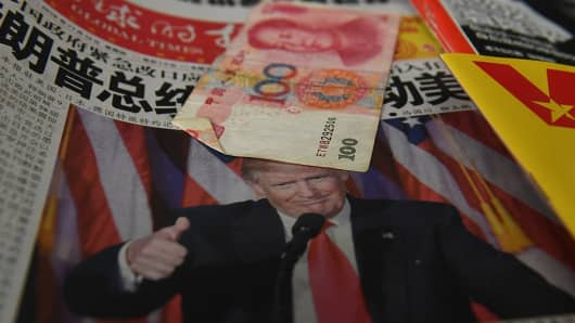 A Chinese newspaper featuring a photo of US President-elect Donald Trump that reads 'President Trump shakes America', is partially covered by a 100 Yuan note on a news stand in Beijing on November 10, 2016.