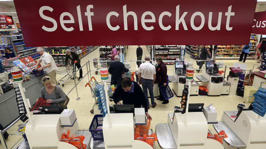 Customers use self checkout desks to pay for goods after shopping inside a Sainsbury's supermarket store.