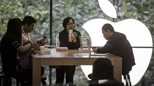 Customers look at the Apple iPhone 7 and iPhone 7 Plus at an Apple Store in Shanghai, China.