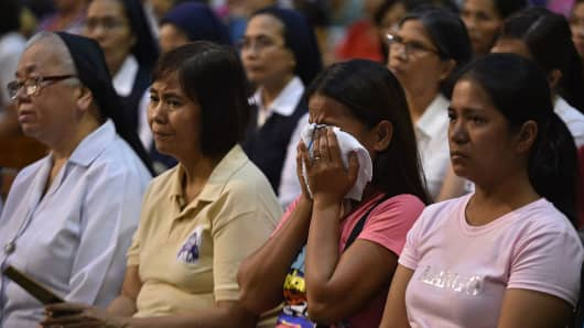 A relative of a victim of extrajudicial killings mourns during a mass offered for all the victims of extra judicial killings, at a church in Manila on November 23, 2016.
