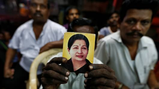 A supporter of Tamil Nadu Chief Minister Jayalalithaa Jayaraman holds her photo at the AIADMK party office in Mumbai, India, December 5, 2016.