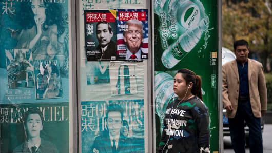 A youth wearing a shirt that reads 'we have nothing in common' walks past a news stand advertising local Chinese magazine Global People, showing cover portraits of Sun Yat-sen (centre L), founding father of the Republic of China, and US president-elect Donald Trump (centre R