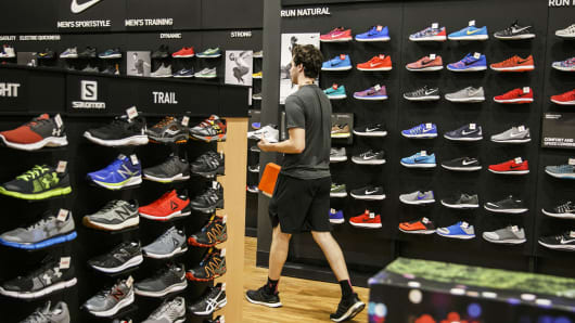 An employee carries Nike sneakers for a customer at a Dick's Sporting Goods store in Sterling Heights, Michigan.