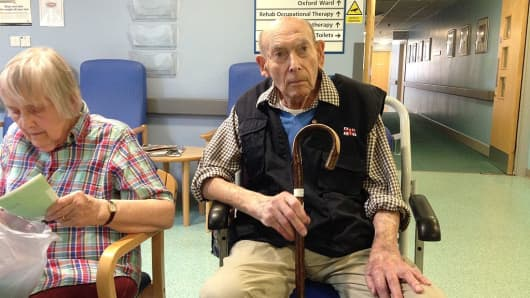 Elderly couple in hospital waiting room.