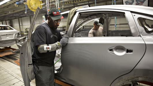 Workers install doors on a Nissan Altima mid-size vehicle at the company's North America manufacturing plant in Canton, Mississippi.