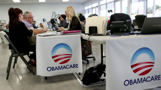 People sit with an insurance advisor as they sign up for the Affordable Care Act in 2015.