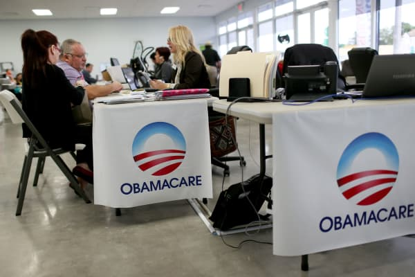 People sit with an insurance advisor as they sign up for the Affordable Care Act, also known as Obamacare, in Miami.