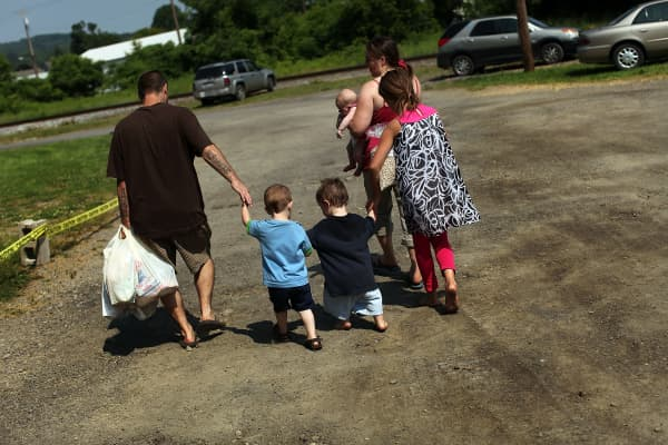 A family walking home with bags of food after a food distribution by the Food Bank of the Southern Tier Mobile Food Pantry in Oswego, New York.