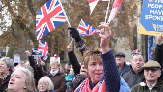 Pro-Brexit demonstrators wave Union Jack flags as they protest outside the Houses of Parliament on November 23, 2016 in London, England.