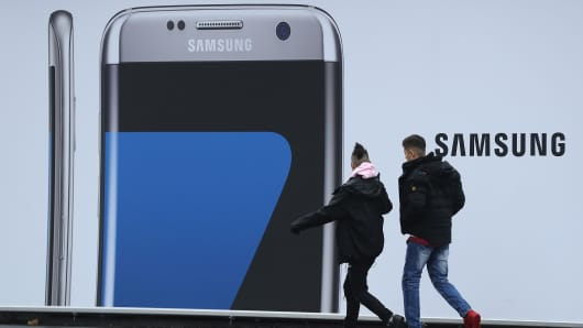 People walk past an advertisement for the Samsung Galaxy S7 Edge smartphone on November 1, 2016 in Berlin, Germany.