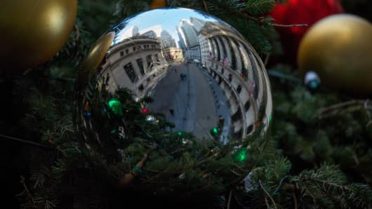 The New York Stock Exchange (NYSE) is reflected in an ornament hanging from a Christmas tree on Broad Street in New York.