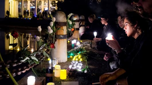 Mourners place flowers and candles during a vigil honoring those who died in a warehouse fire in Oakland, California on December 5, 2016.