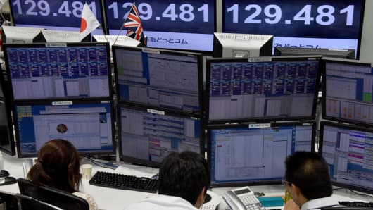 Traders ckeck computer screens showing the Japanese yen rate against the British pound at a brokerage in Tokyo on October 7, 2016.