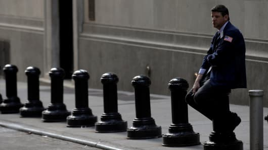 A trader takes a break on Wall Street outside the New York Stock Exchange.