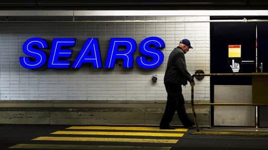 A man walks by a Sears store.