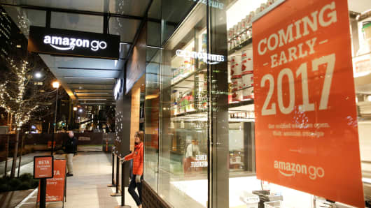 An Amazon employee is pictured outside the Amazon Go grocery store in Seattle, December 5, 2016.
