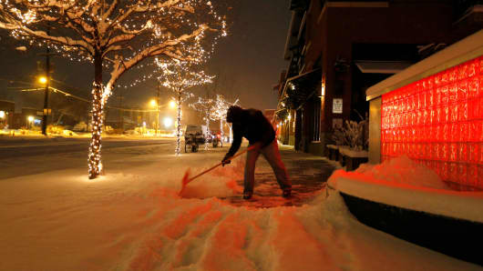Before dawn, Rick Velasquez shovels fresh snow during a winter storm in Boulder, Colo., Wednesday, Dec. 7, 2016.