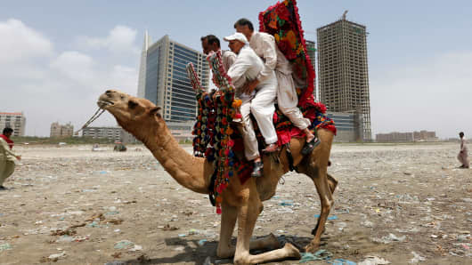 Men sit on a camel as they prepare to take a ride along Clifton beach in Karachi, Pakistan.