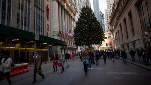 Pedestrians walk near a Christmas tree in front of the New York Stock Exchange (NYSE) in New York.