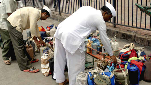 Dabbawallas arranging lunchboxes in crate, Mumbai, India.