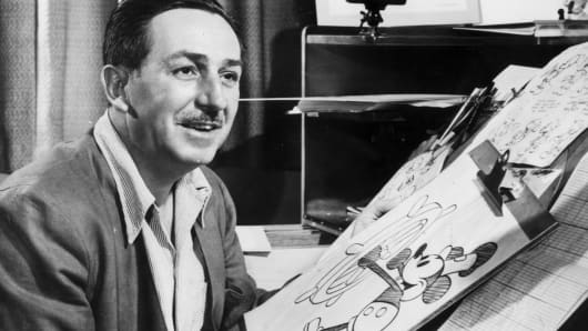 American animator and motion picture studio founder Walt Disney (1901 - 1966) sits at his drawing board in his studio, drawing a sketch of his character Mickey Mouse, Burbank, California.