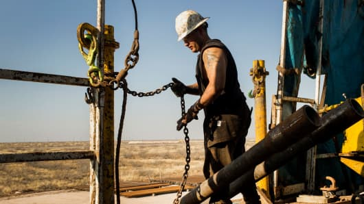 A worker prepares to lift drills by pulley in the Permian basin outside of Midland, Texas.