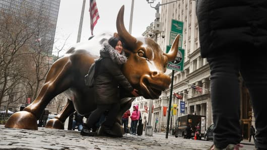 Tourists take a picture with the market bull near the New York Stock Exchange in New York City.