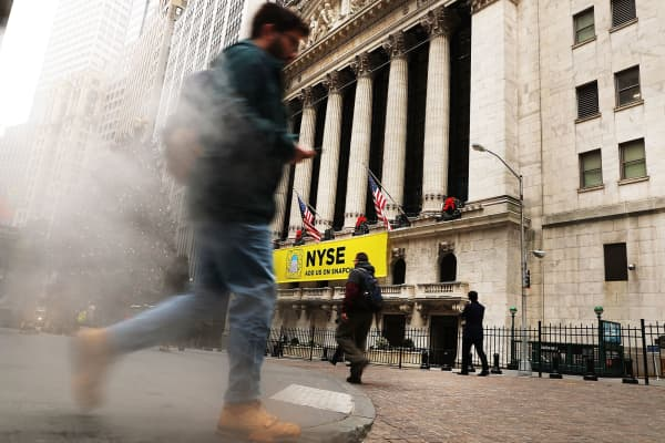 People walk outside of the New York Stock Exchange in New York City.